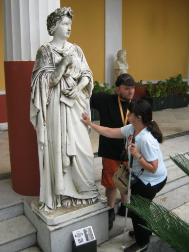 Tony and Tatiana touching a statue.