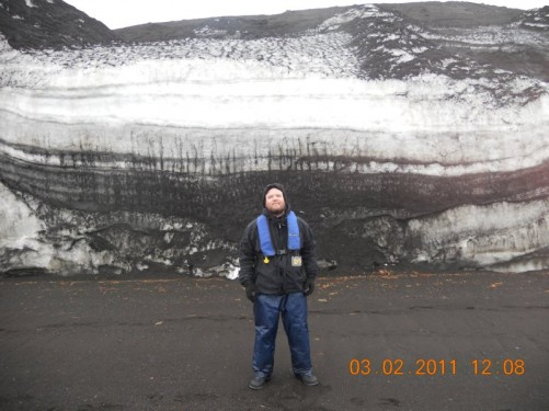 Tony standing in front of Telefon Ridge. The ridge is made up of layers: some predominantly white with ice and others almost black due to the dark volcanic rock and sediment.