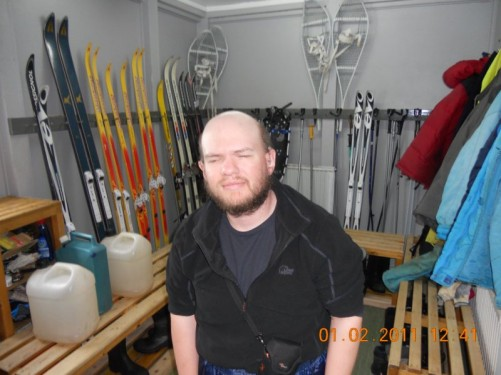 Tony in a room with skis and other outdoor equipment.
