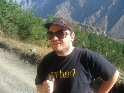 Tony beginning climb, snow peaked mountains including Mount Kazbek in background