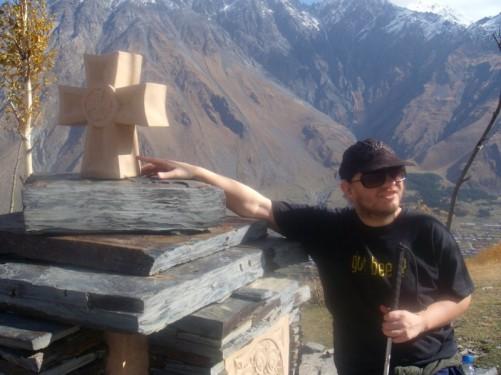 Tony by a stone cross outside Tsminda Sameba Church.