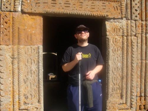 Tony standing in a finely carved stone doorway at Tsminda Sameba Church.