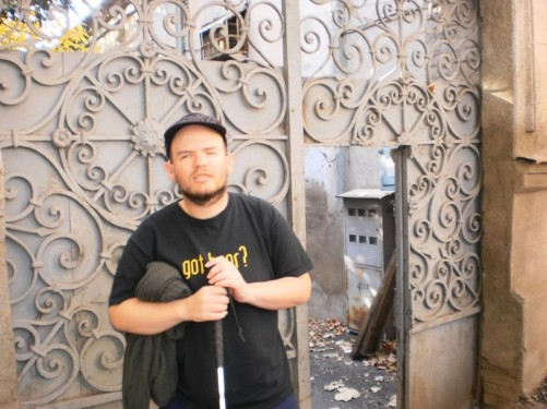 Tony outside the large metal gates to a residential building.