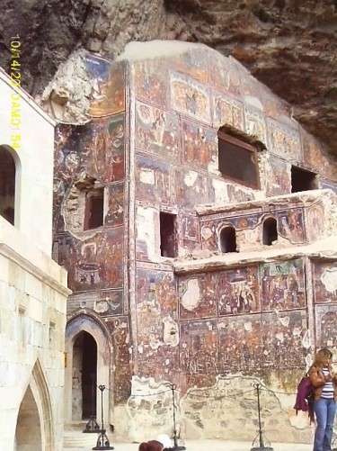 The Rock Church at Sumela Monastery built into a cliff with painted exterior walls.