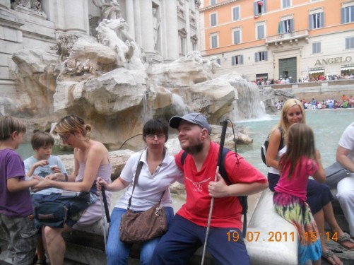 Tony and Tatiana sitting on the edge of the Trevi Fountain.