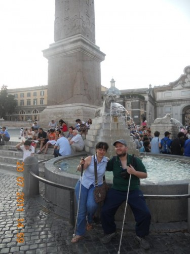 Piazza del Popolo in the evening. Tony and Tatiana sat on the edge of one of the fountains of the centrally located Fontana dell'Obelisco.