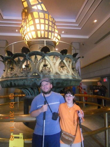 Tony, Tatiana in the Statue of Liberty Museum with the statue's original torch behind.