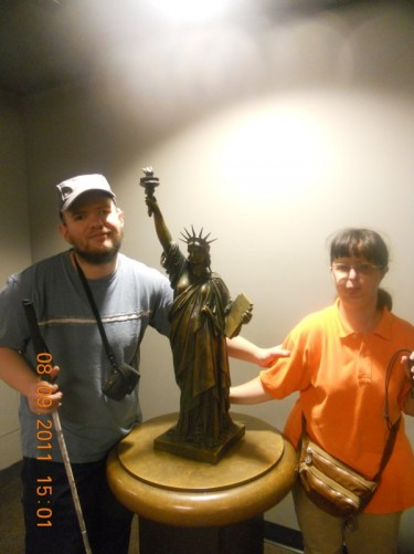 Tony, Tatiana beside a model of the Statue of Liberty. The model can be touched, which enables blind and visually impaired people to gain an impression of what the actual statue looks like.
