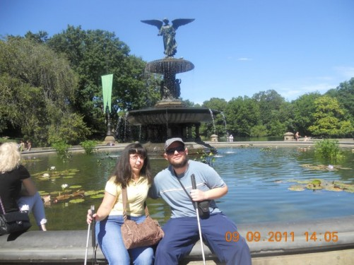 Tony, Tatiana sat on the edge of Dethesda Fountain with the Angel of the Waters sculpture, at Dethesda Terace in the centre of Central Park.