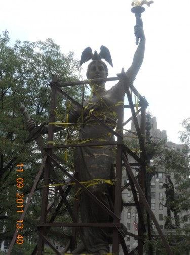 Large, bronze, female figure holding a torch, The Victory Statue. It is usually on top of the Soldiers and Sailors Monument, but has been removed for repairs.