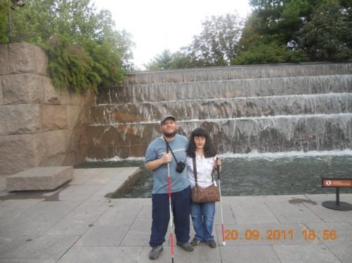 Tony, Tatiana in front of a waterfall.