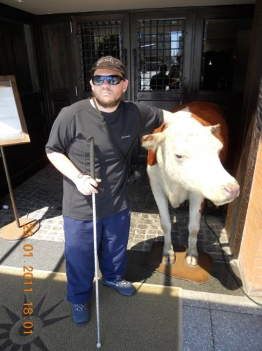 Tony touching a stuffed cow outside another restaurant.