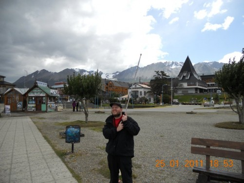 Tony holding his cane in the air at the waterfront, Ushuaia buildings and the Martial Mountains in the background.