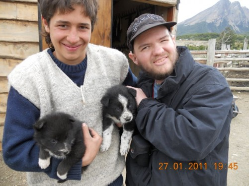 Tony with one of the horse riding instructors - the instructor is holding two puppies.