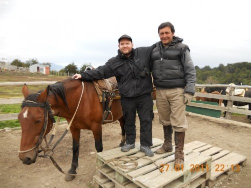 Tony standing by a horse with an instructor.