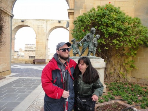 Tony and Tatiana in the Upper Barrakka Gardens. Behind is a bronze statue of three children. It is titled Les Gavroches (The Urchins) and is by Maltese sculptor Antonio Sciortino (1849-1947).