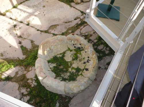 Looking down at a stone object, like a large bowl. Tarxien temples complex.