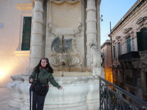 Tatiana in front of the fountain with an eagle in the corner of St. George's Square.
