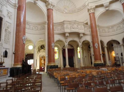 Interior of the Basilica of Our Lady of Mount Carmel - including rows of seats and marble columns.