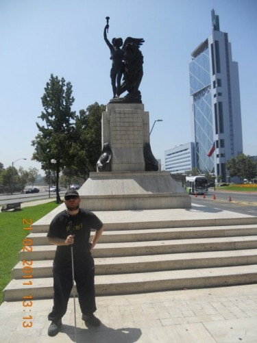 Tony in front of a statue of an angel holding a torch standing alongside a lion, Plaza Italia. This monument is intended to symbolise the friendship between the peoples of Italy and Chile and dates from 1910.