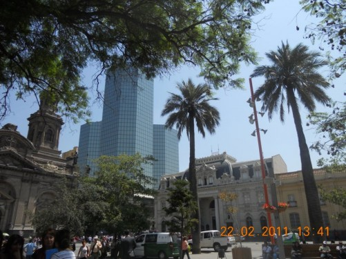 Looking towards the Metropolitan Cathedral of Santiago (Spanish: Catedral Metropolitana de Santiago) and a tall glass-clad office building located along side.
