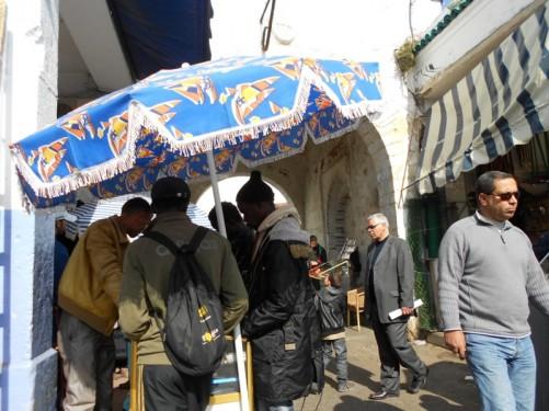 Narrow medina street. People standing around a stall.