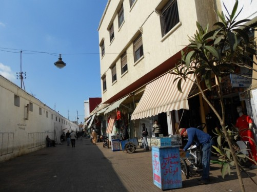 Looking along a street in the medina. There are shops along one side, and on the other, the rear of a long single storey building.