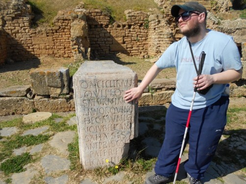 Tony touching a Roman stone block with a Latin inscription on the front.