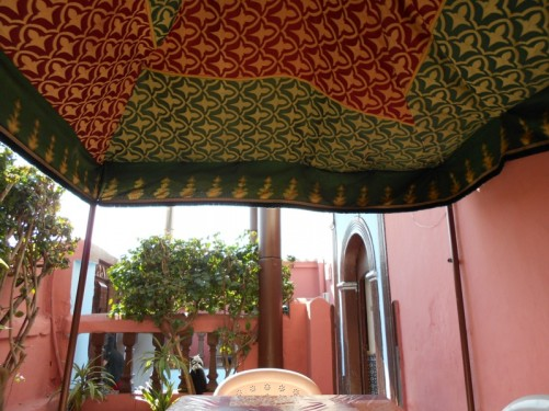 A small patio area. Photo taken sitting at a table under a sun umbrella. Part of HI Rabat Hostel, Rabat.