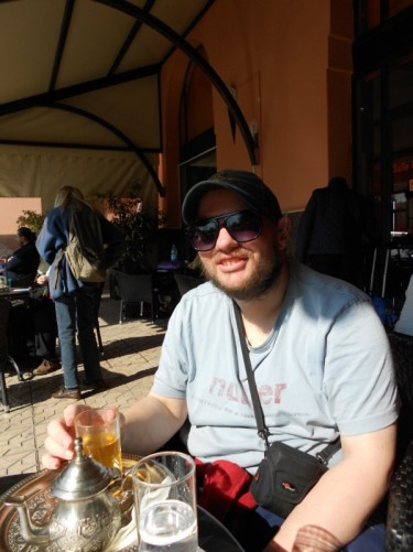 Tony drinking Moroccan tea at an outdoor table near Marakesh train station.