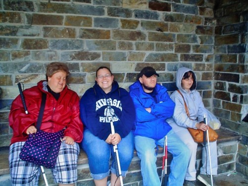 Lora, Angela, Tony, Tatiana, sitting under a shelter with stone walls. Waiting for the ferry to Dartmouth.