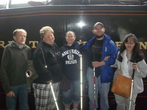 Lora and Angela, both from Kentucky USA, with Tony, Tatiana, and Paul, stood by a steam train. Painton train station on the platform of the Dartmouth Steam Railway.