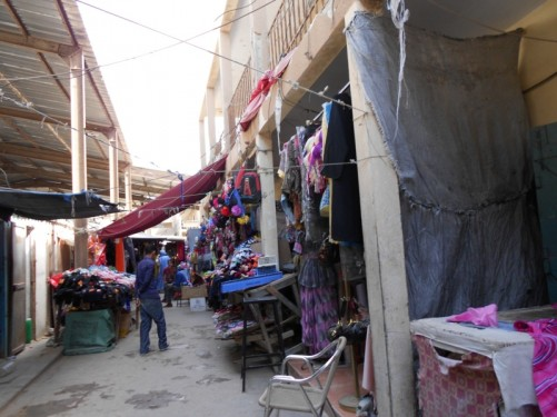 A narrow street with shops and stalls, mostly selling clothes. In or around Nouadhibou market.