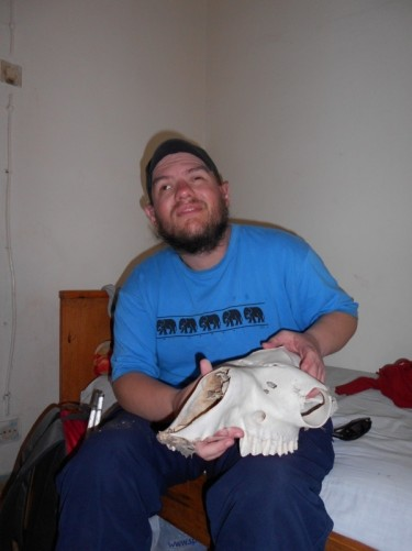 Tony sitting on a bed holding a camel's skull.  It's placed outside the guesthouse to give protection!
