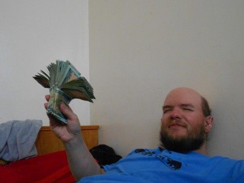 Tony lying on a bed in the guesthouse, holding a large wad of money and looking like a gambler!