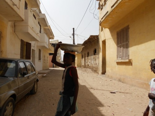 A dusty side street. A girl walking past carrying a bowl on her head.