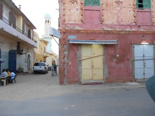 Looking into a dusty street with the minaret of a small mosque a little way along.