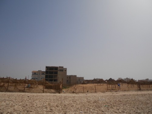Looking towards wooden sun shelters at the top of the beach, surrounded by net fences. Buildings beyond.