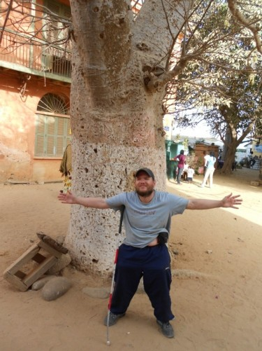 Tony standing with arms outstretched in front of a large Bouback tree. A square in Gorée.