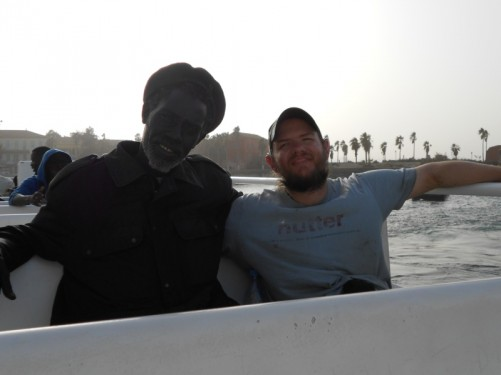 Tony sitting with a local man on the boat back to Dakar.