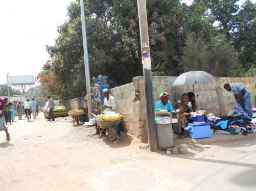 People at the side of a road selling clothes, fruit and other goods.
