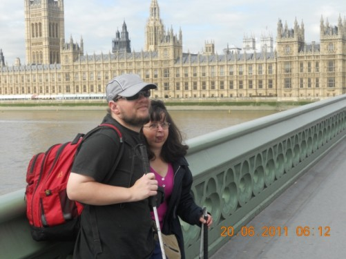 Tony and Tatiana standing on Westminster Bridge. View of the Palace of Westminster (Houses of Parliament).