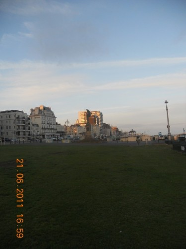 Grass by the sea front promenade, looking towards the Peace Statue and bandstand.