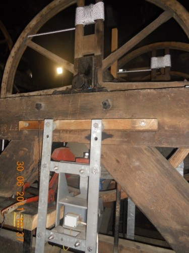 The wooden structure to which the bells are attached, including a large wheel, which is rotated by pulling a rope to ring one of the bells.