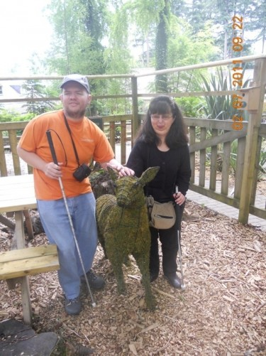 Tony and Tatiana touching a deer sculpted from plant material.