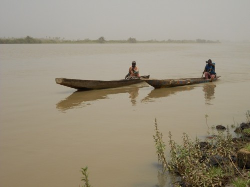 View across the wide Gambia River. Two local men paddling canoes are approaching.