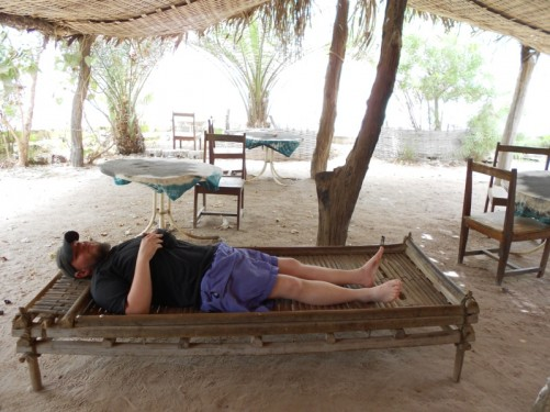 Tony relaxing on a traditional wooden sun bed at Kairoh Garden Guesthouse.