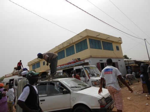 In the centre of Wassu. Luggage being loaded on to the roofs of minibuses.