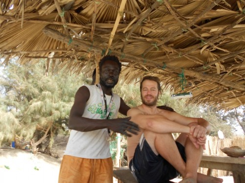 Simon and a local guy under a shelter, part of Ibby's bar on the beach.