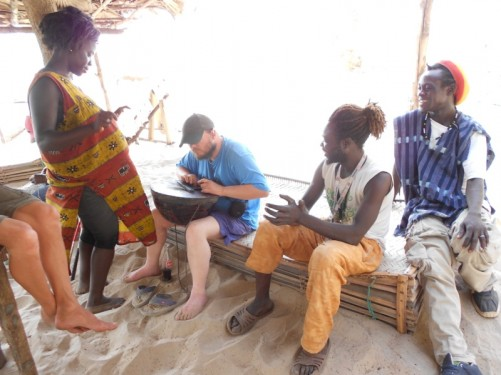 Tony playing a calabash, with two local guys and Khady. Sitting under the shelter on the beach.